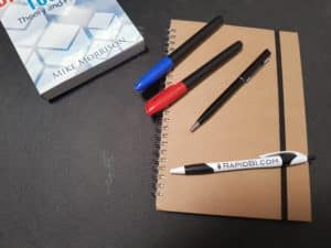 Photo of note book and pens - Guest Blogging for RapidBI